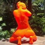 orange sculpture of a woman kneeling wearing a bikini