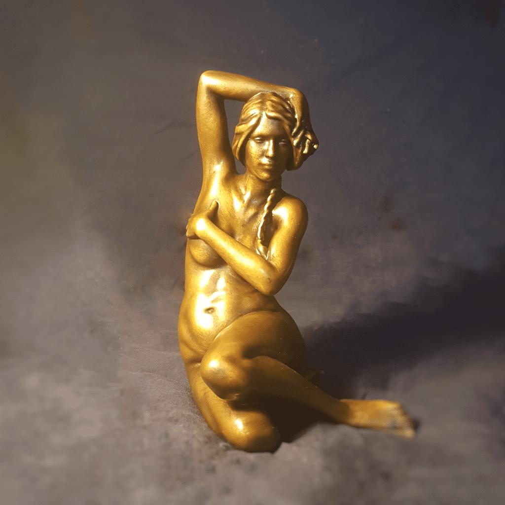 bronze figurine of a nude woman sitting