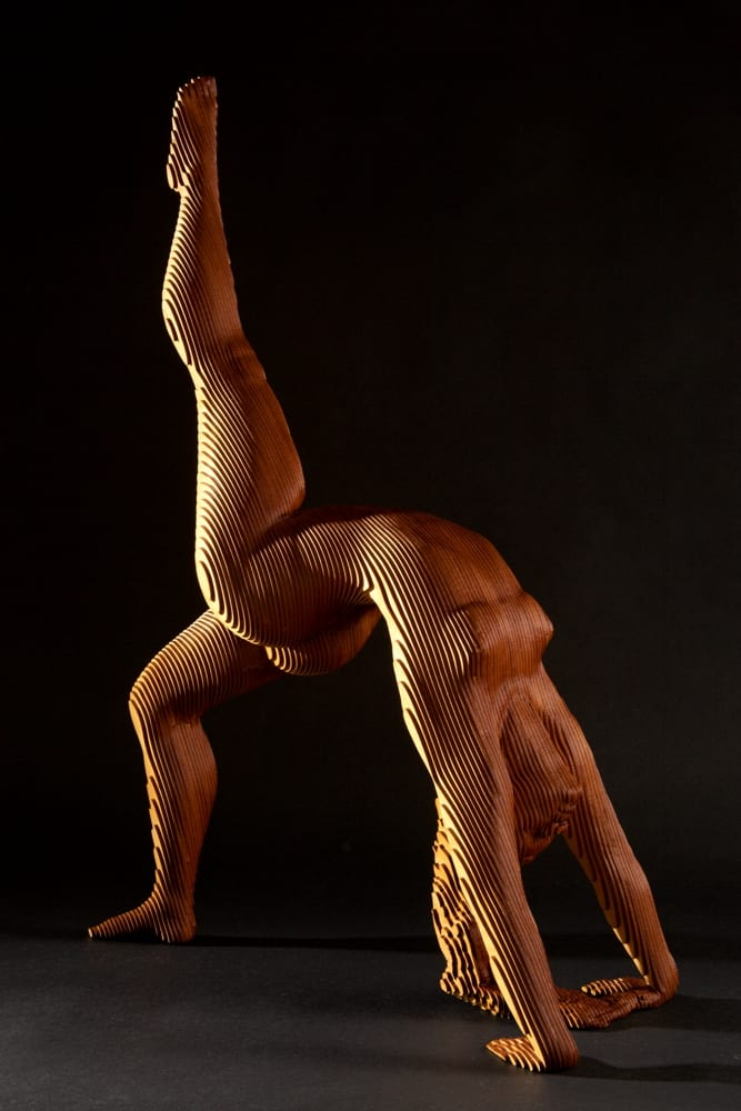 wood sculpture of a nude woman in a yoga pose