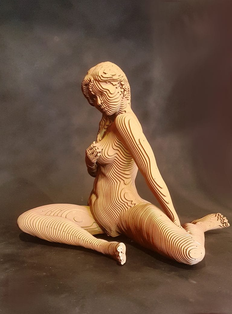 A wooden sculpture of a nude woman sitting and holding her breast.