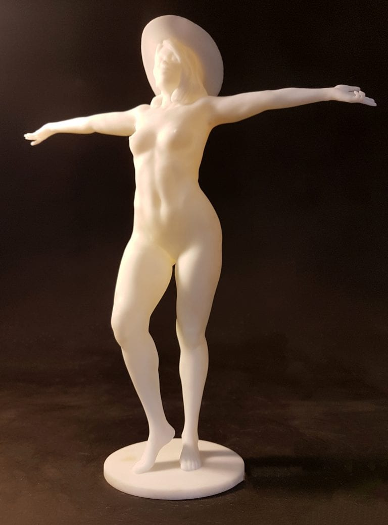 Figurine of a nude woman wearing a hat, standing and spreading her arms out.
