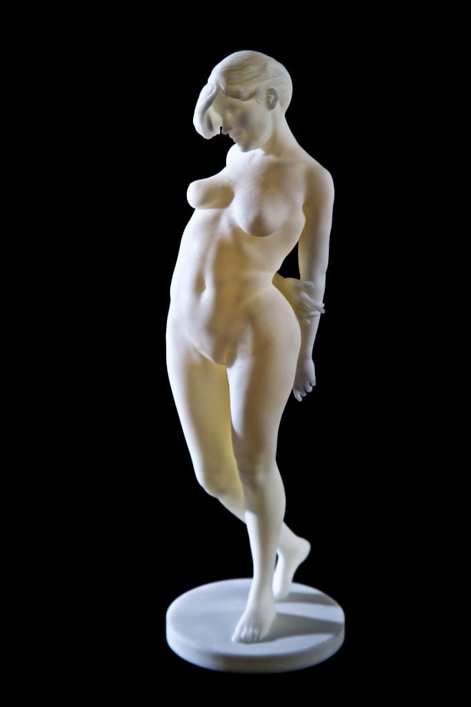 white statuette of a nude woman standing