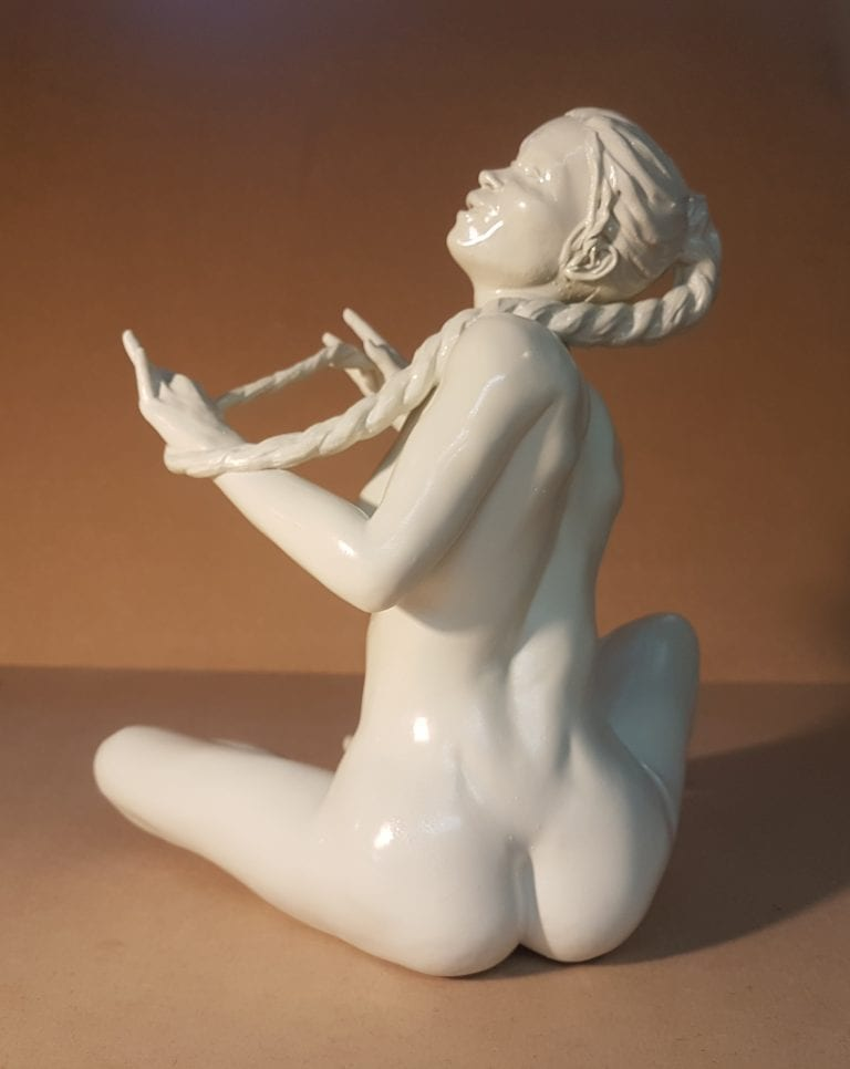 A sitting nude woman holding a long braid in her hands