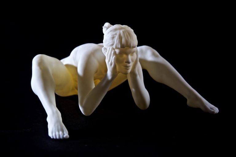 a white sculpture of a nude young woman sitting and leaning forward