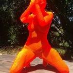 an orange sculpture of a woman kneeling wearing a bikini
