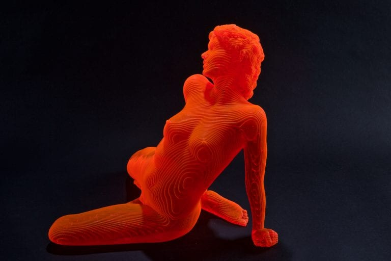 an orange sculpture of a nude woman sirring and leaning backwards