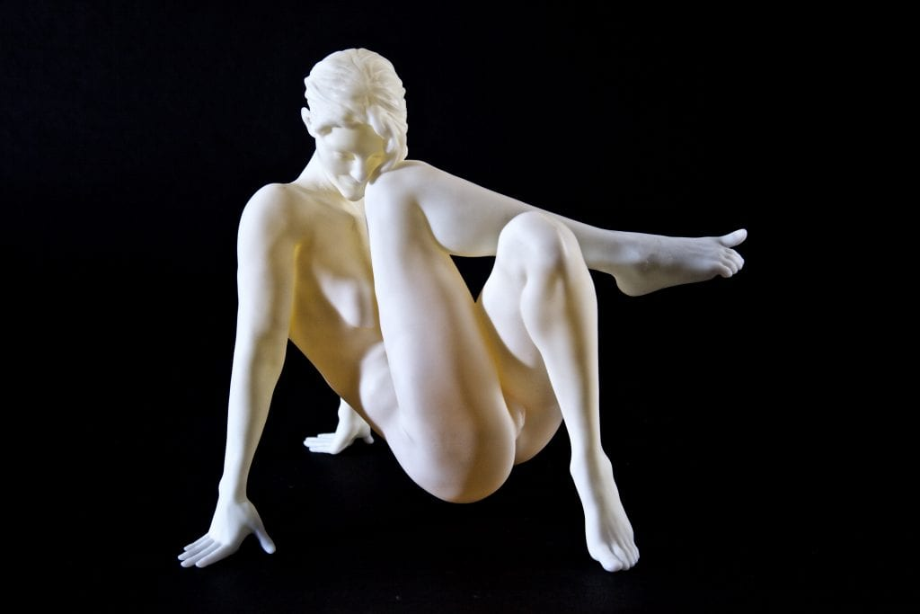 a sculpture of a nude woman leaning backwards on her hands