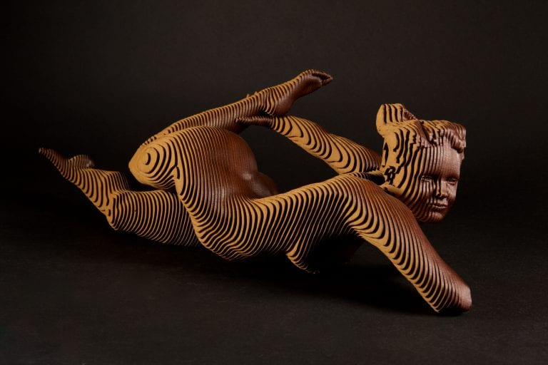 Wooden sculpture of a nude woman lying on her belly