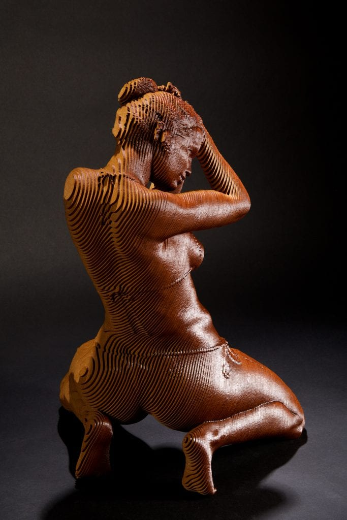 sculpture of a woman kneeling, wearing a bikini