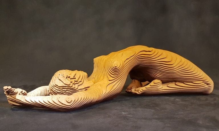 wooden sculpture of a nude woman arching backwards