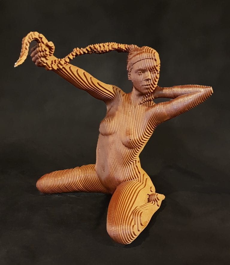 a nude woman kneeling and pulling her long braid