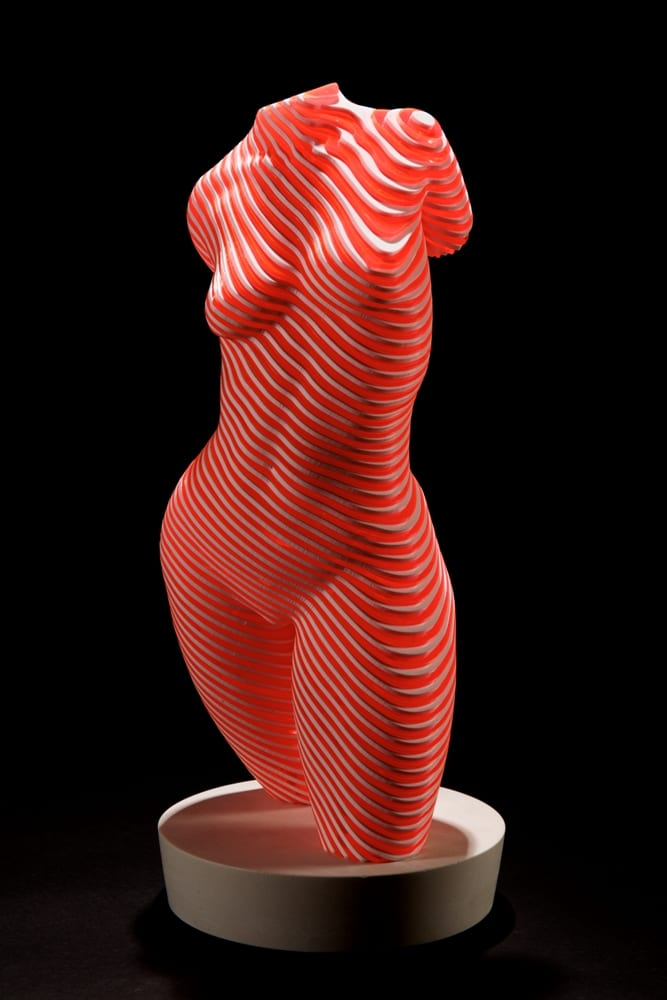 white and pink sculpture of nude female torso