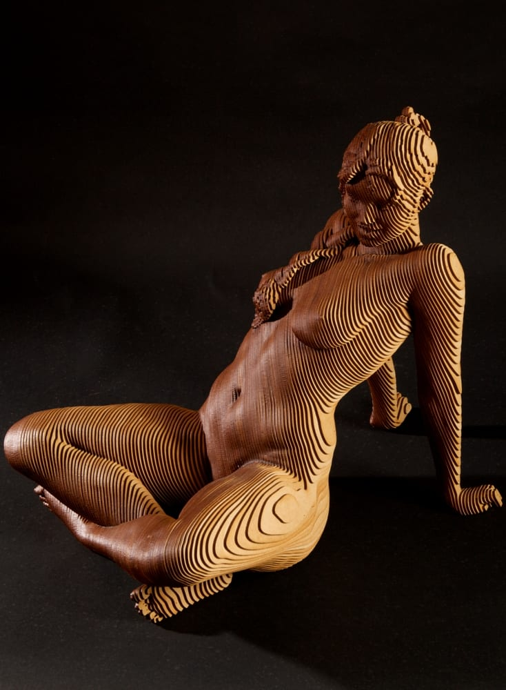 A wood sculpture of a nude woman sitting and leaning back