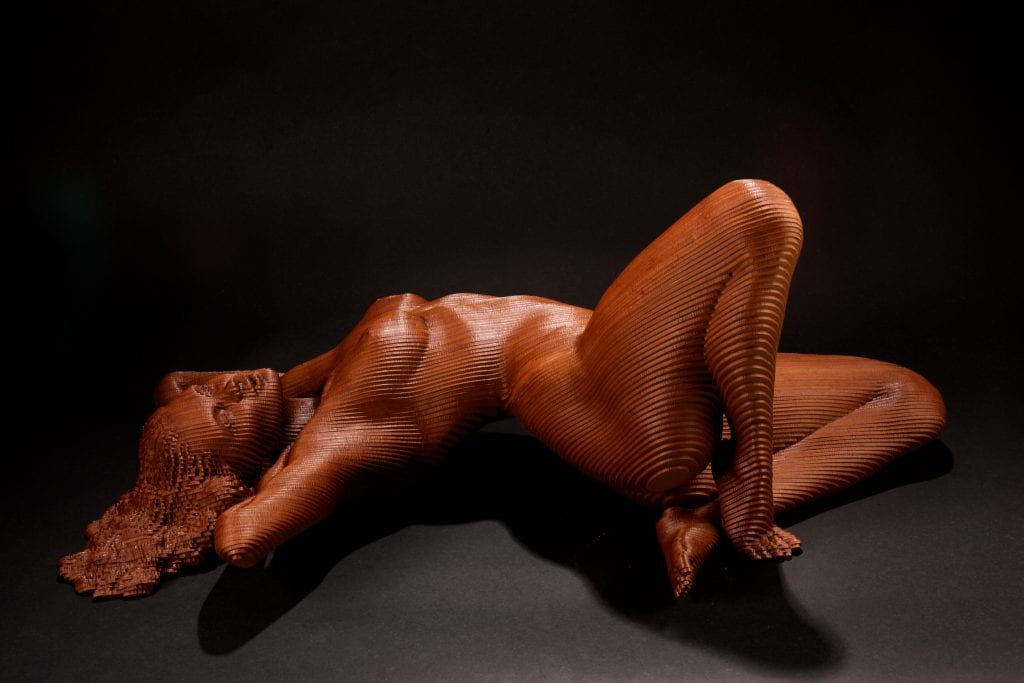 a wooden sculpture of nude woman reclining on her back