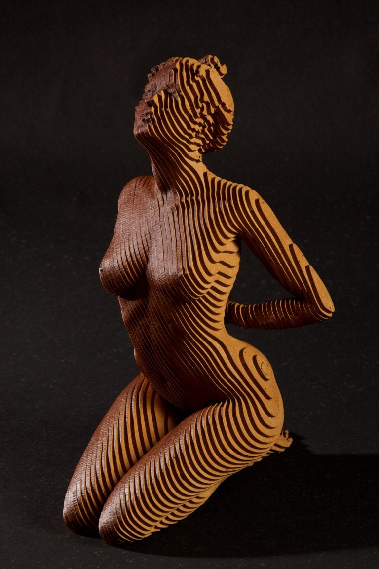a small wooden statue of a nude woman kneeling