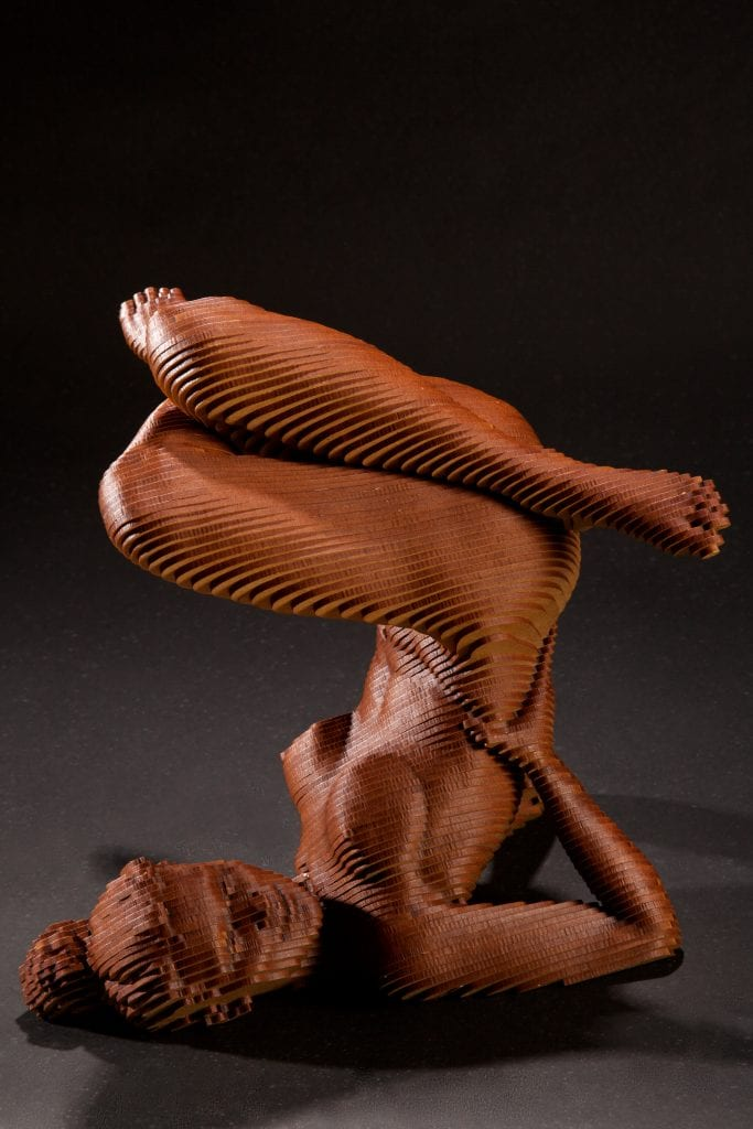 Wooden sculpture of a nude woman on her back