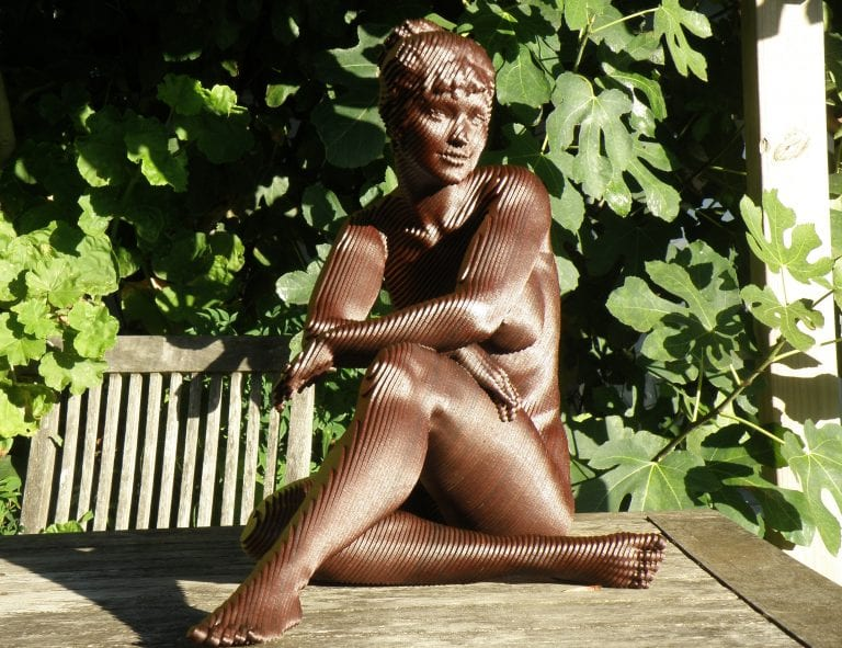 a wooden sculpture of a nude woman sitting
