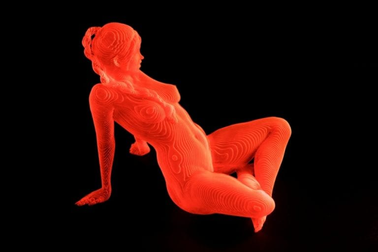 an orange acrylic sculpture of a nude woman sitting