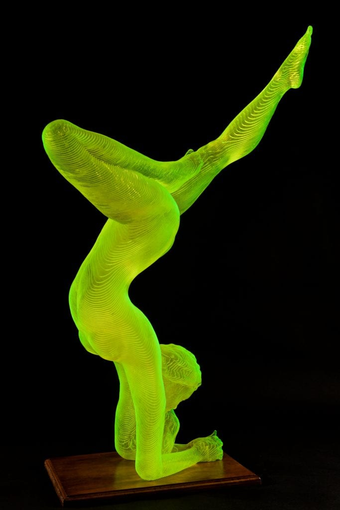 yellow sculpture of a nude woman in a yoga pose legs up