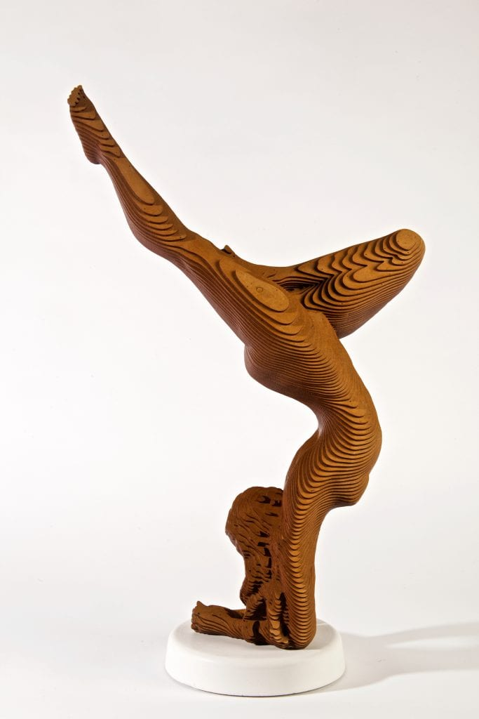 wood sculpture of a nude woman doing a yoga headstand