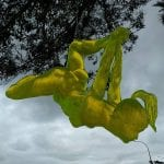 yellow acrylic sculpture hanging from a tree