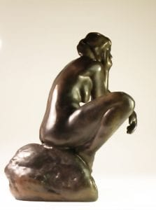 a bronze sculpture of a nude woman sitting as Rodin's thinker