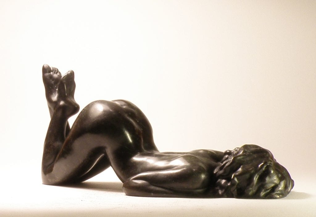a bronze figurine of a nude woman lying on her belly