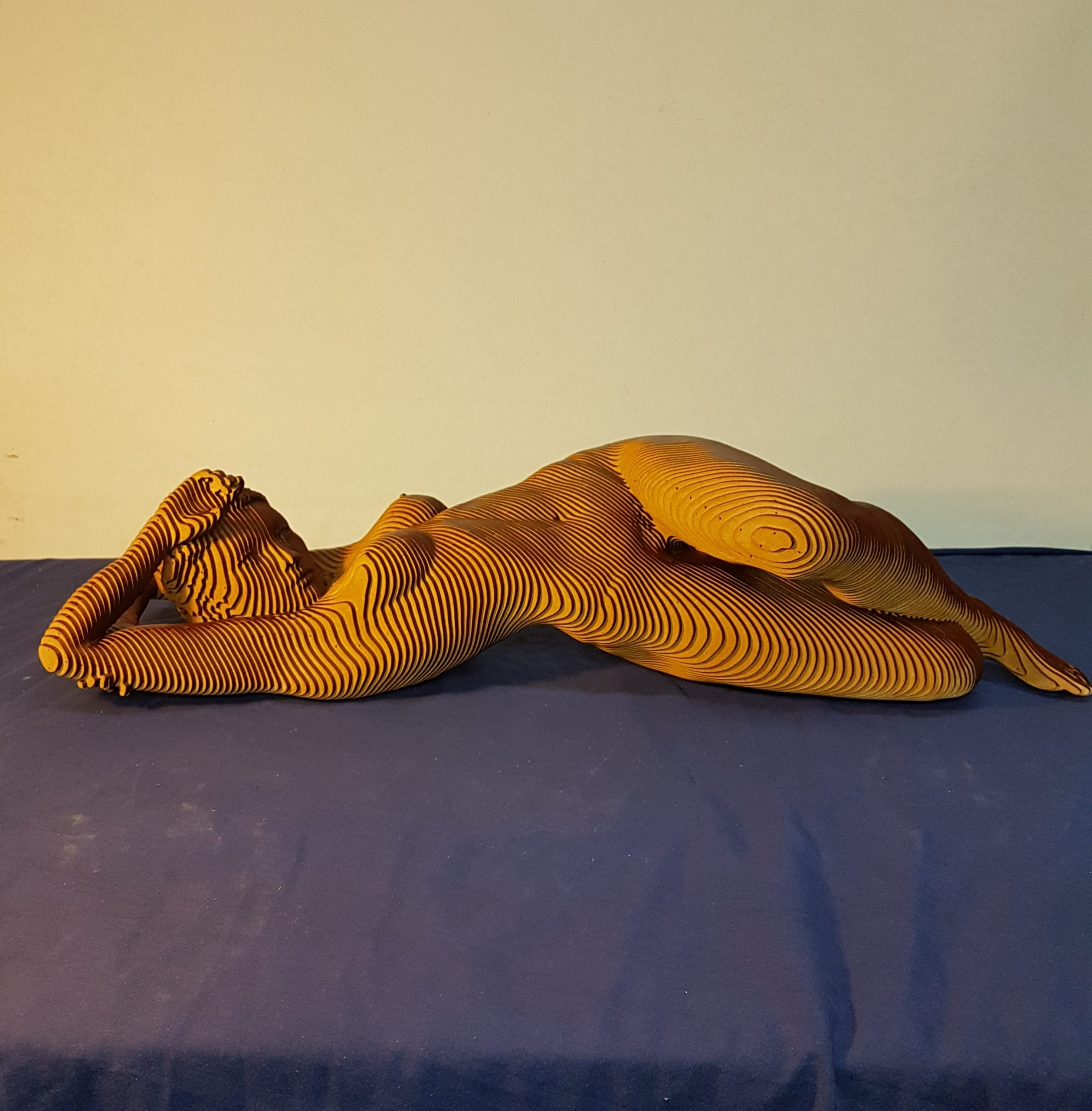 wooden sculpture of a nude woman reclining