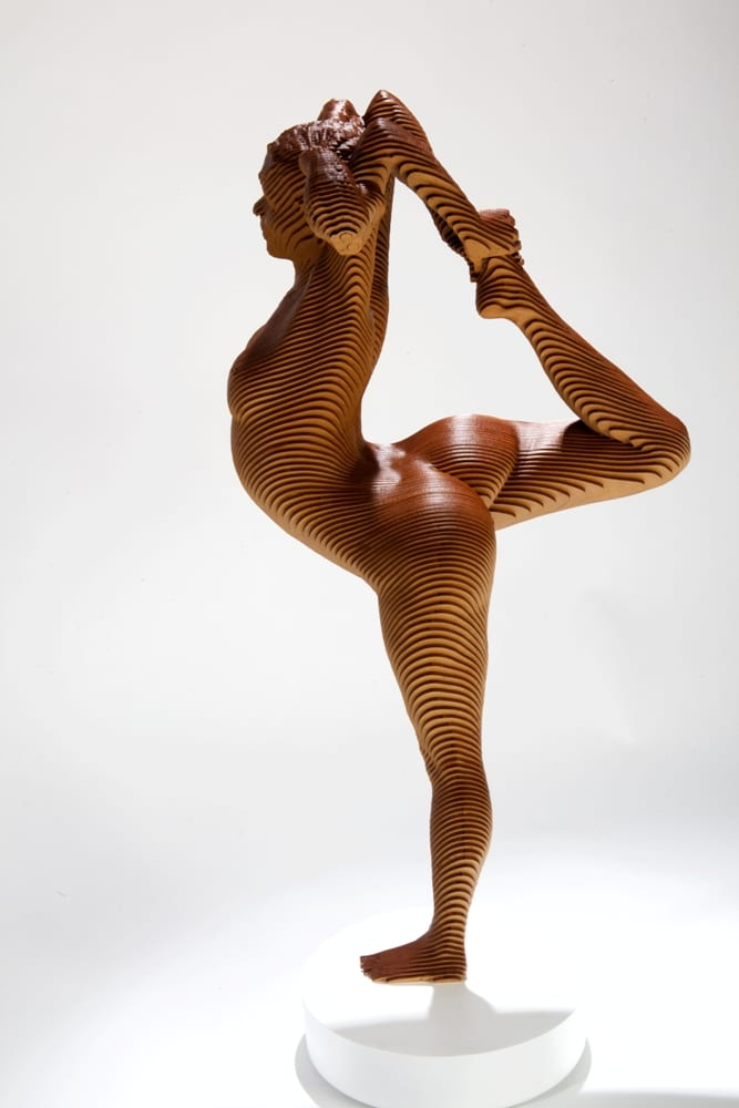 wood sculpture of a nude woman standing