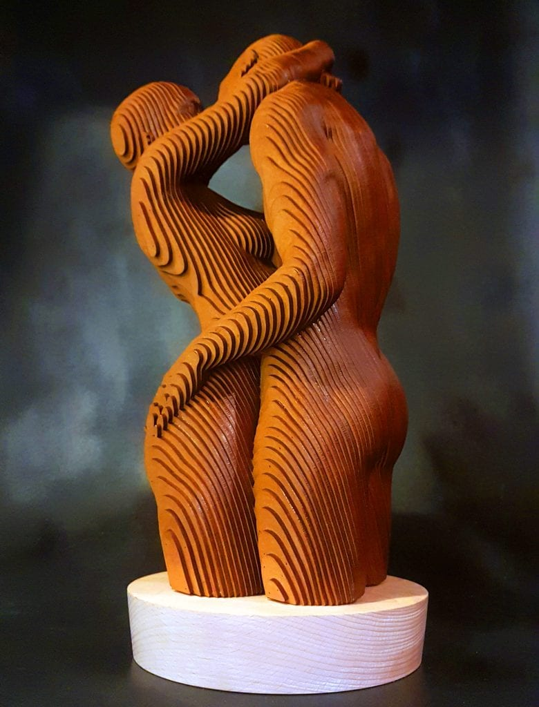 Wooden sculpture of a couple kissing